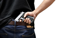 The man pulls out a gun. Tucked in his pant Stock Photos