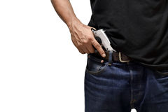 The man pulls out a gun. Tucked in his pant Stock Images