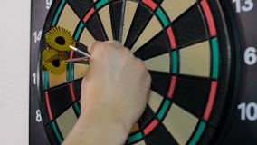Man pulls out yellow darts from the board stock video