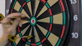 Man pulls out yellow darts from the board stock footage