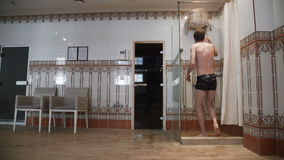 The man pulls the rope and pours the water out of the bucket. Cold shower in after sauna. Concept of a healthy lifestyle. Luxury spa holidays stock video footage