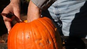 Man pulls seeds from Halloween pumpkin stock footage