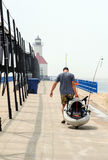 A man pulls a small boat down a long pier near a light house in Michigan Stock Images