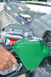 A man pumping gas in to the tank Stock Images