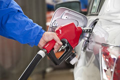 Man Pumping Gasoline Into Silver Car With Red Fuel Nozzle Stock Photography