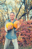 Man with  pumpkins having fun Stock Images