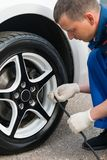 Man pumps a wheel at the car, observes a norm of pressure in tires stock image