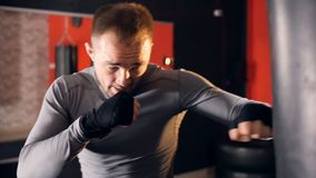 A man punches a heavy bag in deep concentration. A man trains in a boxing gym with a heavy bag stock footage
