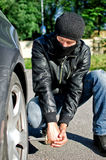 Man punctures a car tyre. Man in mask punctures a car tyre. Revenge concept Stock Photo