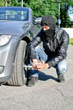 Man punctures a car tyre. Man in mask punctures a car tyre. Revenge concept Royalty Free Stock Photography