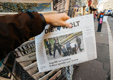 Man purchases Die Zeit newspaper from press kiosk after London a Stock Photo