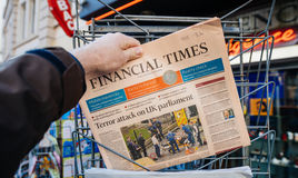 Man purchases Financial times newspaper from press kiosk after L Royalty Free Stock Images