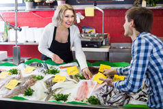 Man purchasing chilled on ice fish in supermarket. Young american men purchasing chilled on ice fish in supermarket stock images