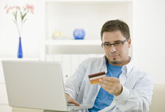 Man purchasing by credit card. Casual man at home using laptop computer purchasing by credit card Stock Photo