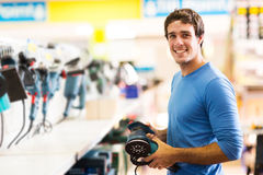 Man purchasing hand tool. Smiling young man purchasing a hand tool in hardware shop Stock Image