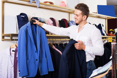 Man purchasing jacket. Young smiling man purchasing jacket at clothing shop Royalty Free Stock Photo
