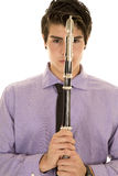 Man in purple dress shirt eyes on both sides of a hatchet close stock photo