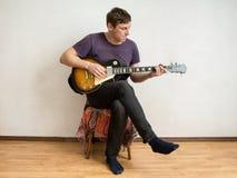 A man in a purple shirt playing guitar Stock Photo