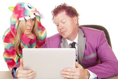 Man purple suit computer woman pajamas over shoulder smirk. A women in a monster costume looking over a business man's shoulder while he is working royalty free stock photos