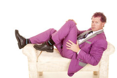 Man purple suit lay on white bench looking Royalty Free Stock Photos