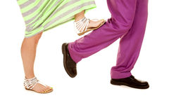 Man purple suit woman green dress feet her stop on calf Royalty Free Stock Images