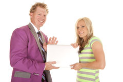 Man purple suit woman green dress holding a laptop Stock Image