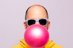 Man with purple sunglasses blowing pink chewing gum and facing the camera Stock Image