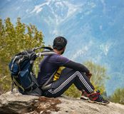 Man in Purple T-shirt With Blue Backpack Sitting on Gray Boulder stock photos