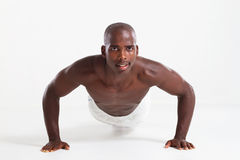 Man push up. Muscular young african american man doing push up exercise against white background royalty free stock photos