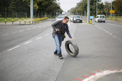 Man Pushes The Car Tire On Street Royalty Free Stock Image