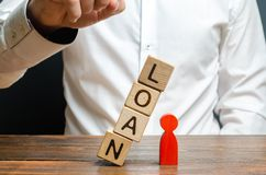 Man pushes downs a cube tower with the word Loan on the red man figure. Lack of protection for vulnerable groups of the population. Debt pit. Harassment of the stock photo