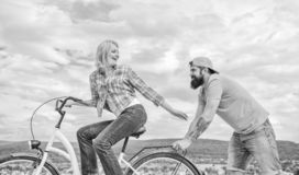 Man pushes girl ride bike. Girl cycling while man support her. Support helps believe in yourself. Feel impulse to start. Man pushes girl ride bike. Girl cycling stock photo
