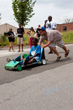 Man Pushes Kid Steering Car In Atlanta Soap Box Derby. Atlanta, GA, USA - August 3, 2013:  A man pushes a kid steering a toy car down a hilly street in the Cool Stock Image