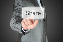 Man pushes virtual share button. On dark background stock images