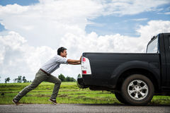 Man pushing a broken car down the road.  Royalty Free Stock Photos