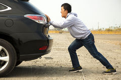 Man pushing a broken car down the rock road Stock Image