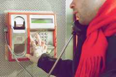 Man pushing buttons on public phone. Young man pushing buttons on public phone Stock Photo