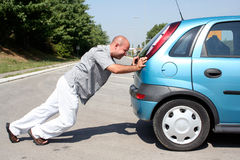 Man pushing a car. Man pushing a broken car or a car out of gas Stock Images