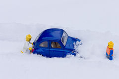 Man pushing car stuck in snow. Toy models. Royalty Free Stock Photography