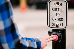 A man pushing a crosswalk button that reads, Stock Photos