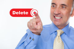 Man pushing the delete button. With a sarcastic grin in his face Royalty Free Stock Images