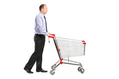 Man pushing an empty shopping cart. A full length portrait of a man pushing an empty shopping cart isolated on white background Stock Photo