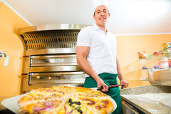 Man pushing the finished pizza from the oven Stock Photos