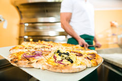 Man pushing the finished pizza from the oven Royalty Free Stock Photos