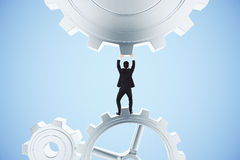 Man pushing gears in the mechanism on a blue background Royalty Free Stock Images