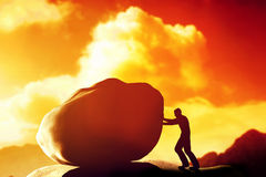 Man pushing a giant, heavy rock over the mountain. Royalty Free Stock Photos