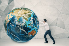 Man pushing globe in concrete room with white floor Stock Image