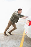Man pushing his broken down car Stock Photography