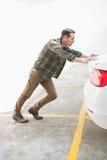 Man pushing his broken down car Stock Photography