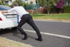 Man pushing his broken down car Stock Images